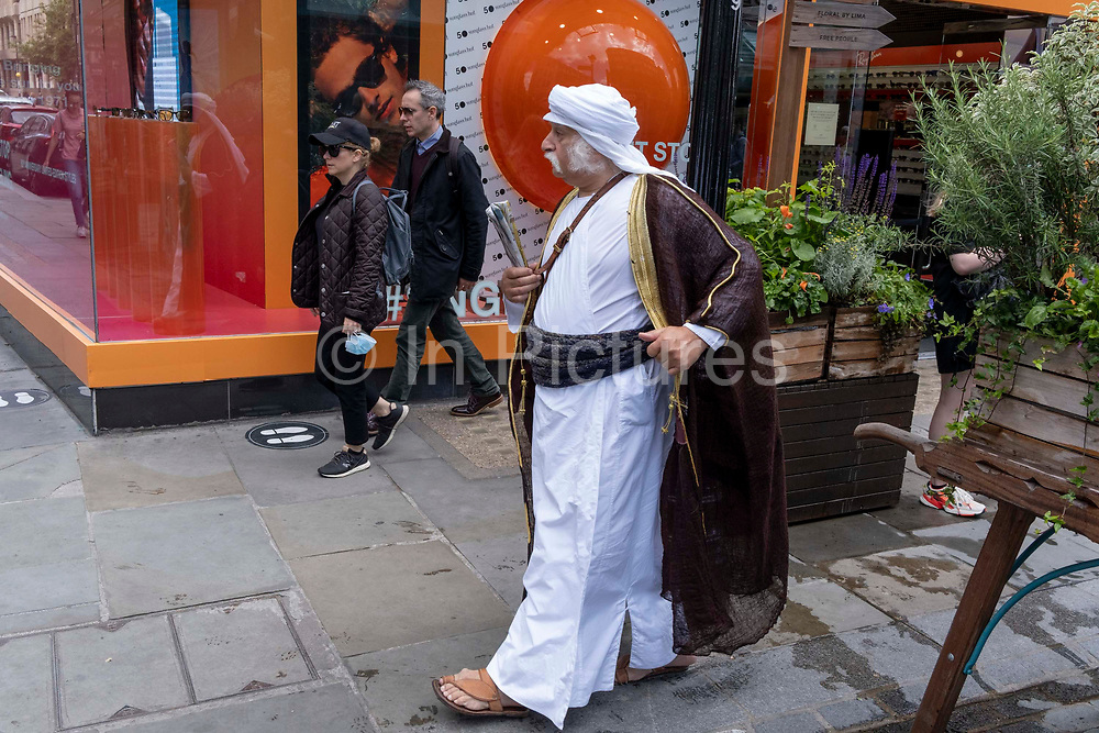 A man dressed in the robes from a Middle-Eastern region walks past the exterior of Sunglass Hut in Covent Garden, on 23rd June 2021, in Westminster, London, England.