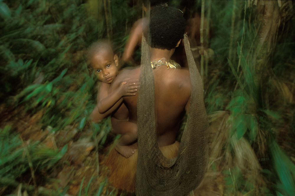 A Kombai woman carries a child on her hip during a hunting and foraging trip in the rainforest in Papua, Indonesia. September 2000. The Kombai are a so-called treehouse people who build their homes high up in the trees. The woman also carries a string bag in which to put foodstuff or her child when it gets sleepy.