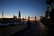 View across the River Thames at night towards The Shard, which is lit up red. London, UK. The Shard and it's neighbouring Tower Bridge are to iconic landmarks on the London skyline.