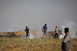 July 28, 2017 - Jabalia, Gaza - A Palestinian protesters throw gas bombs at Israeli soldiers during clashes on the Israeli border with the Gaza Strip, Friday, July 28, 2017. Gaza's Health Ministry says a Palestinian teen was killed in clashes with Israeli soldiers stationed near the strip's border fence with Israel. (Credit Image: © Nidal Alwaheidi/Pacific Press via ZUMA Wire)