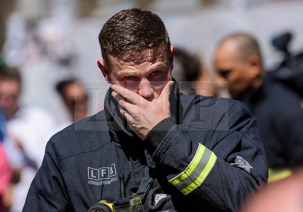 © Licensed to London News Pictures. 19/06/2017. London, UK. Firefighters who attended the scene of the fire join relatives of the victims and members of the public to observe minutes silence held near the scene of the Grenfell tower block fire. The blaze engulfed the 27-storey building killing dozens - with 34 people still in hospital, many of whom are in critical condition. Photo credit: Ben Cawthra/LNP