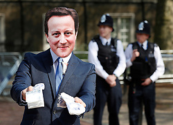 © Licensed to London News Pictures. 12/05/2016. London, UK. A protestor dressed as Prime Minister David Cameron offers fake money as he stands outside the anti- corruption summit. The real Mr Cameron is hosting a one day summit which is addressing world corruption. Photo credit: Peter Macdiarmid/LNP
