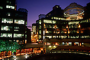 A wide dusk landscape of the development in the City of London, known as Broadgate is a vast estate of corporate buildings developed in the Thatcher years, sitting astride the redeveloped Liverpool Street mainline station. Broadgate is a large, 32-acre (13 ha) office and retail estate in the City of London, owned by British Land and the Blackstone Group and managed by Broadgate Estates. The original developer was Rosehaugh: it was built by a Bovis / Tarmac Construction joint venture and was the largest office development in London until the arrival of Canary Wharf in the early 1990s. The modern and mainly-pedestrianised development is located on the original site of Broad Street station (closed in 1986) and beside and above the railway approaches into Liverpool Street station.
