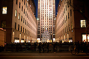 Crowds pack the promenade to see the Rockefeller Christmas tree, with 30 Rockefeller Center in the background.