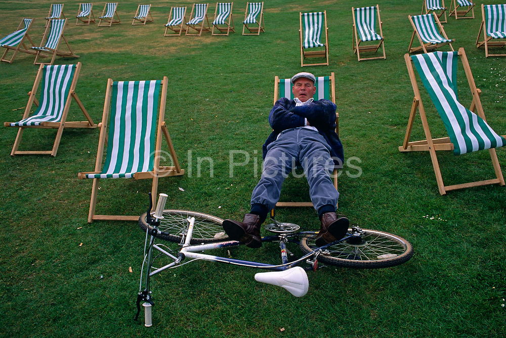 An eccentric middle-aged man rests his legs on his bicycle while -open mouthed and snoring - snatches forty winks on a striped deck chair in London's Hyde Park, England. We look down on the grass which is still green and lush  on this summer's day in the heart of the city. He is wearing a flat cap with trousers (pants)  tucked in his socks for his next bicycle journey. He is a quintissentially English sunbather enjoying a quiet snooze in a public park open space.