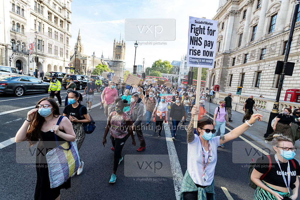 Nurses as well as care workers from St Thomas' Hospital, wearing face protective surgical masks to curb the spread of coronavirus pandemic, hold placards as they march towards Number Ten in Downing Street to protest for a pay rise in London, Wednesday, July 29, 2020. Health care unions are launching a campaign for a pay rise for NHS (National Health Service) nurses and care workers. NHS demonstration was also supported by the Black Lives Matter activists. (VXP Photo/ Vudi Xhymshiti)