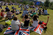 Brits enjoy a hot summer to watch live Boxing coverage from a large tv screen in the Olympic Park during the London 2012 Olympics. Sitting on union jack flags they sit on green grass located on a hilltop. London's Olympic Park, at just under a square mile, is the largest new park in the city for more than 100 years. The planting of 4,000 trees, 300,000 wetland plants and more than 150,000 perennial plants plus  nectar-rich wildflower make for a colourful setting for the Games. This land was transformed to become a 2.5 Sq Km sporting complex, once industrial businesses and now the venue of eight venues including the main arena, Aquatics Centre and Velodrome plus the athletes' Olympic Village. After the Olympics, the park is to be known as Queen Elizabeth Olympic Park.