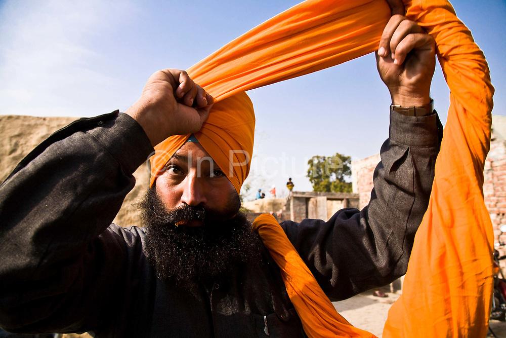 A Sikh man prepares his turban before leaving for work, Chita Kalaan village, Punjab, India