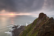 Dramatic skies and the setting sun above Hartland Point's lighthouse. Devon, England, UK.