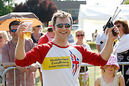 Photo by Andrew Tobin/Tobinators Ltd - 07710 761829 - New 2013 World Champion Rob Bresler celebrates during the World Peashooting Championships held at Witcham, Cambridgeshire, UK on 13th July 2013. Run in conjunction with the village fair, the Championships have been held in Witcham since 1971 when they were started by a Mr Tyson, the village schoolmaster, in order to raise funds for the village hall.Competitors come from as far afield as the USA and New Zealand to attempt to win the event. The latest technology is often used, including laser sights and titanium and carbon fibre peashooters. All peashooters must conform to strict length rules, not exceeding 12 inches, and have to hit a target 12 feet away. Shooting 5 peas at a plasticine target attached to a hay bale, the highest scorers move through the initial rounds to a knockout competition, followed by a sudden death 10-pea shootout.