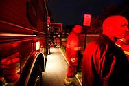 Firefighters stand next to a fire truck on an emergency scene