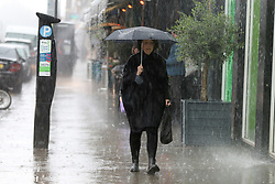 © Licensed to London News Pictures. 17/05/2021. London, UK. A woman shelters from heavy rain beneath an umbrella in north London. More rain is forecast for the South East of England this week. Photo credit: Dinendra Haria/LNP