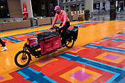 A cyclist with the app-based Pedal Me deliveries company rides his bike across a multicoloured pedestrianised traffic-free street in the City of London, capitals financial district, aka The Square Mile, on 20th October 2021, in London, England.