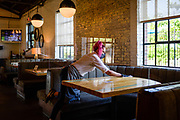 30248072A Nashville, Tenn., - Server Lacy Kowalkowski, sanitizes a table at Pinewood Social. Pinewood Social has taken steps to socially distance in their restaurant and take temperatures of every patron that walks through the door.