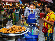 "12 JANUARY 2016 - BANGKOK, THAILAND: A fried banana vendor in Khlong Toey Market in Bangkok. Khlong Toey (also called Khlong Toei) Market is one of the largest ""wet markets"" in Thailand. The market is located in the midst of one of Bangkok's largest slum areas and close to the city's original deep water port. Thousands of people live in the neighboring slum area. Thousands more shop in the sprawling market for fresh fruits and vegetables as well meat, fish and poultry.         PHOTO BY JACK KURTZ"