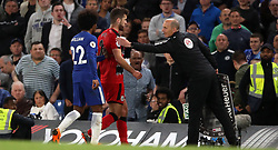 Chelsea's Willian and fourth official Mike Dean usher Huddersfield Town's Tommy Smith off the pitch as he is substituted during the Premier League match at Stamford Bridge, London.
