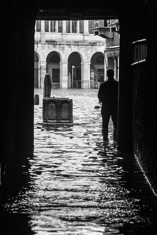 Venice, Italy. 29 October, 2018. A man watch the level of the water in a small flooded square during the high tide on October 29, 2018, in Venice, Italy. This is a selection of pictures of different areas of Venice that the press has not covered, were resident live and every year they have to struggle with the high tide. Due to the exceptional level of the 'acqua alta' or 'High Tide' that reached 156 cm today, Venetian schools and hospitals were closed by the authorities, and citizens were advised against leaving their homes. This level of High Tide has been reached in 1979. © Simone Padovani / Awakening / Alamy Live News
