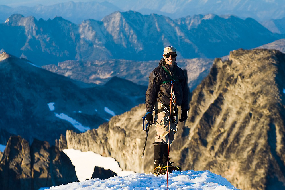 Jim Prager stands atop the thin snow ridge near the summit of Eldorado Peak in the heart of the North Cascades National Park, Washington, the setting sun highlighting the rocky ridges in the distance below.