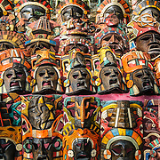 Market stalls selling wooden masks and other local souvenirs and handicrafts to tourists visiting Chichen Itza Mayan ruins archeological site in Mexico.