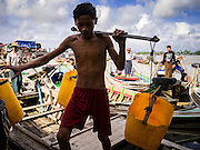 13 JUNE 2013 - YANGON, MYANMAR:     A boy carries a yoke for carrying motor oil out to boatmen at the Aung Mingalar Jetty in Yangon. The jetty is a stop for commuters who live on the far side of the Irrawaddy River and ride small boats back and forth across the river. Yangon, formerly Rangoon, is Myanmar's commercial capital and used to be the national capital. The city is on the Irrawaddy River and has a vibrant riverfront.   PHOTO BY JACK KURTZ