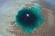 "SANSHA, CHINA - JULY 24: <br /> <br /> A marine expert jumps into the Sansha Yongle Blue Hole to do exploration on July 24, 2016 in Xisha Islands, Sansha City, Hainan Province of China. Sansha municipal government has named the world\'s deepest ocean blue hole as ""Sansha Yongle Blue Hole\"" which is located around the Yongle atoll of the Xisha Islands. The hole has a vertical depth of 300.89 meters, a diameter of 130 meters on the surface, and its bottom\'s diameter is 36 meters. No connection between the hole and the outside sea has been found so far and the water inside the hole has no obvious flow. <br /> ©Exclusivepix Media"