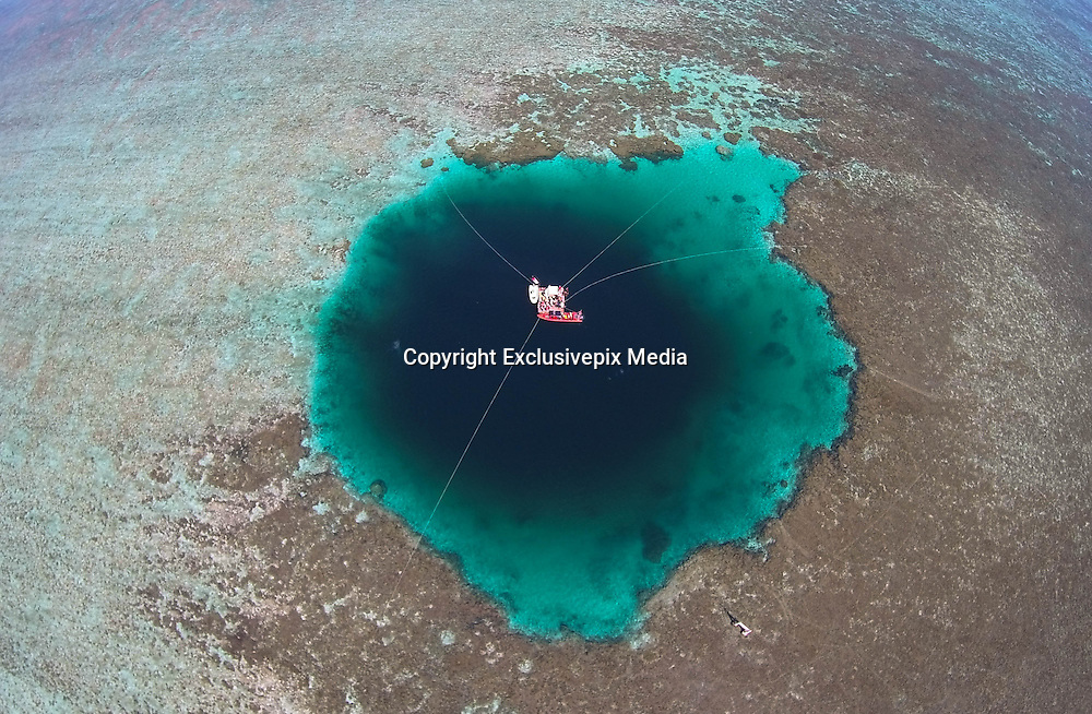 """SANSHA, CHINA - JULY 24: <br /> <br /> A marine expert jumps into the Sansha Yongle Blue Hole to do exploration on July 24, 2016 in Xisha Islands, Sansha City, Hainan Province of China. Sansha municipal government has named the world\'s deepest ocean blue hole as \""""Sansha Yongle Blue Hole\"""" which is located around the Yongle atoll of the Xisha Islands. The hole has a vertical depth of 300.89 meters, a diameter of 130 meters on the surface, and its bottom\'s diameter is 36 meters. No connection between the hole and the outside sea has been found so far and the water inside the hole has no obvious flow. <br /> ©Exclusivepix Media"""
