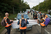 A vehicle is driven slowly towards Insulate Britain climate activists blocking a slip road from the M25, causing a long tailback on the motorway, as part of a new campaign intended to push the UK government to make significant legislative change to start lowering emissions on 13th September 2021 in Godstone, United Kingdom. The activists, who wrote to Prime Minister Boris Johnson on 13th August, are demanding that the government immediately promises both to fully fund and ensure the insulation of all social housing in Britain by 2025 and to produce within four months a legally binding national plan to fully fund and ensure the full low-energy and low-carbon whole-house retrofit, with no externalised costs, of all homes in Britain by 2030 as part of a just transition to full decarbonisation of all parts of society and the economy.