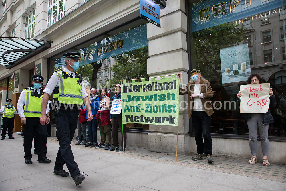 Metropolitan Police officers pass in front of activists from Palestine Action protesting outside the UK headquarters of Elbit Systems, an Israel-based company developing technologies used for military applications including drones, precision guidance, surveillance and intruder-detection systems, on 28th May 2021 in London, United Kingdom. Pro-Palestinian activists had organised the protest against Elbit's presence in the UK and against British arms sales to and support for Israel.