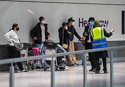 © Licensed to London News Pictures. 15/02/2021. London, UK. Officials escort passengers out of Terminal 5 at London Heathrow this morning as quarantine hotels near Heathrow start to accept passengers from red list countries. From today, (Monday 15 February 2021) anyone arriving from a red-list destination must quarantine at a designated hotel and pay a hotel fee of £1,750 for a 10 day quarantine period. Photo credit: Alex Lentati/LNP