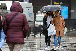 © Licensed to London News Pictures. 03/11/2020. London, UK. Women shelter from rainfall underneath an umbrella in north London. The Met Office forecasts rain and strong winds in the South East of England. Photo credit: Dinendra Haria/LNP
