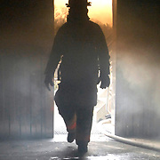 Joseph Thompson, 316th Civil Engineer Squadron fire protection assistant chief of operations, walks through the different layers of smoke in the live fire training building after live fire training March 5, 2010, at Joint Base Andrews Md. Live fire training is a necessary and indispensable tool for the 316th CES firefighters, which provides them with the ability to experience the heat and flames that can be found in a structure fire, but in a controlled environment. (U.S. Air Force photo by Airman 1st Class Perry Aston) (Released)