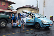 Men help load a car with merchandise bought by elderly women at the local market. Leon, Nicaragua. July 29, 2018.