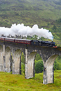 'The Jacobite' locomotive steam train on West Highland Rail crosses famous Glenfinnan Viaduct tourist spot in the Highlands of Scotland