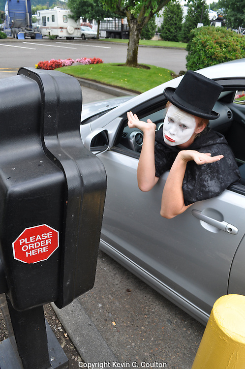 Humorous photograph of a mime trying to place an order at the speaker at a drive-through restaurant illustrating the problem with a mime trying to order food in this manner!