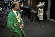 A Racing Post vendor looks over to a young woman wearing a wide-brimmed hat on Ladies Day during Royal Ascot, the annual event on the English sporting and social calendar, on 18th June 1992, in London, England. Royal Ascot is held every June and is one of the main dates on the sporting calendar and English social season. Over 300,000 people make the annual visit to Berkshire during Royal Ascot week, making this Europe's best-attended race meeting. There are sixteen group races on offer, with at least one Group One event on each of the five days. The Gold Cup is on Ladies Day on the Thursday. There is over £3 million of prize money on offer.