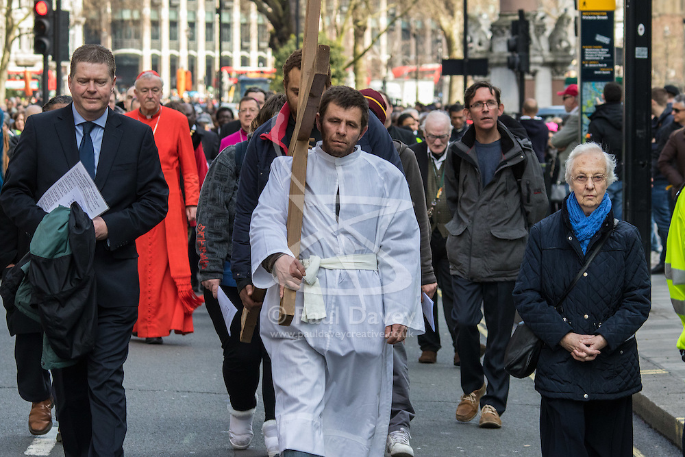 Westminster, London, March 25th 2016. Westminster's annual interdenominational Easter procession takes place with a procession from Methodist Central Hall to Westminster Cathedral and then on to Westminster Abbey, with the cross borne by people from The Passage, a homeless charity. PICTURED: The procession, led by a man from the homeless charity The passage carries the cross towards Westminster Cathedral. <br /> ©Paul Davey<br /> FOR LICENCING CONTACT: Paul Davey +44 (0) 7966 016 296 paul@pauldaveycreative.co.uk