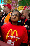 Food service industry workers strike for higher wages on October 4th 2018 in Leicester Square, London, United Kingdom. Day of action by workers from TGI Fridays, McDonalds; Deliveroo and Wetherspoons, supported by TUC and Labour Party, demanding better conditions for the hospitality sector. A woman wears a McStrike t shirt.