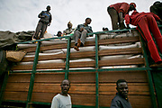 Central Africans load trading goods such as sacks of coals onto a big lorry between Cameroon and Central African Republic. These big lorries, also considered as public transportation, are usually overloaded with luggage and people, causing frequent breakdowns, flat tires, and accidents.