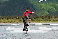 Man in drysuit paddles iceberg down tributary river next to Bear Lake in Kenai Fjords National Park, Alaska.