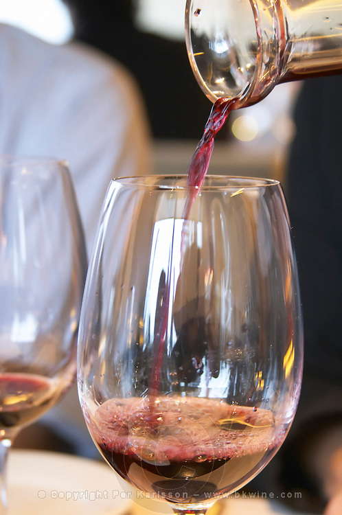 Wine being served in a glass from a decanter. The Restaurant Red at the Hotel Madero Sofitel in Puerto Madero, Buenos Aires Argentina, South America