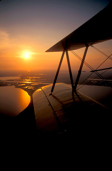 Sunrise/Sunset Silhouette of Wing on Biplane While in Flight
