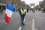 December, 8th, 2018 - Paris, Ile-de-France, France: Demonstrator with French flag on Champs Elysees. The French 'Gilets Jaunes' demonstrate a fourth day. Their movement was born against French President Macron's high fuel increases. They have been joined en mass by students and trade unionists unhappy with Macron's policies. Nigel Dickinson