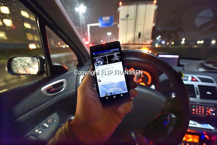 Nederland, Nijmegen, 20-11-2017 Een bestuurder zit in de auto achter het stuur terwijl hij met zijn telefoon, mobieltje, smartphone bezig is. Appen Foto: Flip Franssen