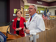 28 DECEMBER 2019 - URBANDALE, IOWA: US Senator ELIZABETH WARREN (D-MA), left, listens to pharmacist JOHN FORBES, owner of the Medicap Pharmacy in Urbandale, IA, talk about changes in law that will allow pharmacists to sell some hearing aids over the counter. Warren was at the pharmacy to announce that legislation she wrote will make hearing aids available over the counter. She said it should make hearing aids less expensive and increase competition in the hearing aid industry. The legislation was co-sponsored by Iowa Republican Senator Chuck Grassley and signed into law by President Trump. Warren is campaigning in Iowa this weekend to support her effort to be the Democratic nominee for the US presidential race in 2020. Iowa traditionally hosts the first presidential selection event of the campaign season. The Iowa caucuses are Feb. 3, 2020.          PHOTO BY JACK KURTZ