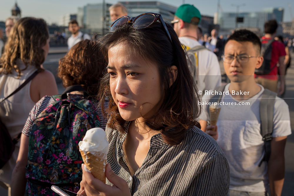 A lady walks over London Bridge with a melting ice cream during an early heatwave in the city, on 19th April 2018, in London, England.