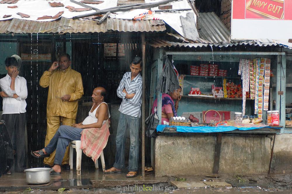 Locals shelter under corrugated iron roof during monsoon rains, Goa, India