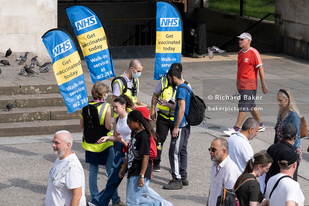 National Health Service (NHS) staff hand out information outside Marble Arch tube station, to encourage the public to go and get vaccinated at a nearby vaccination centre, on 11th August 2021, in London, England.