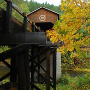 McKee Covered Bridge, built in 1917, in southern Oregon crosses over the Applegate River.  The fall color of the trees leaves can be seen in the trees.  The Applegate River is a 51-mile (82 km) long tributary of the Rogue River. It drains forested foothills of the Siskiyou Mountains along the Oregon-California border.
