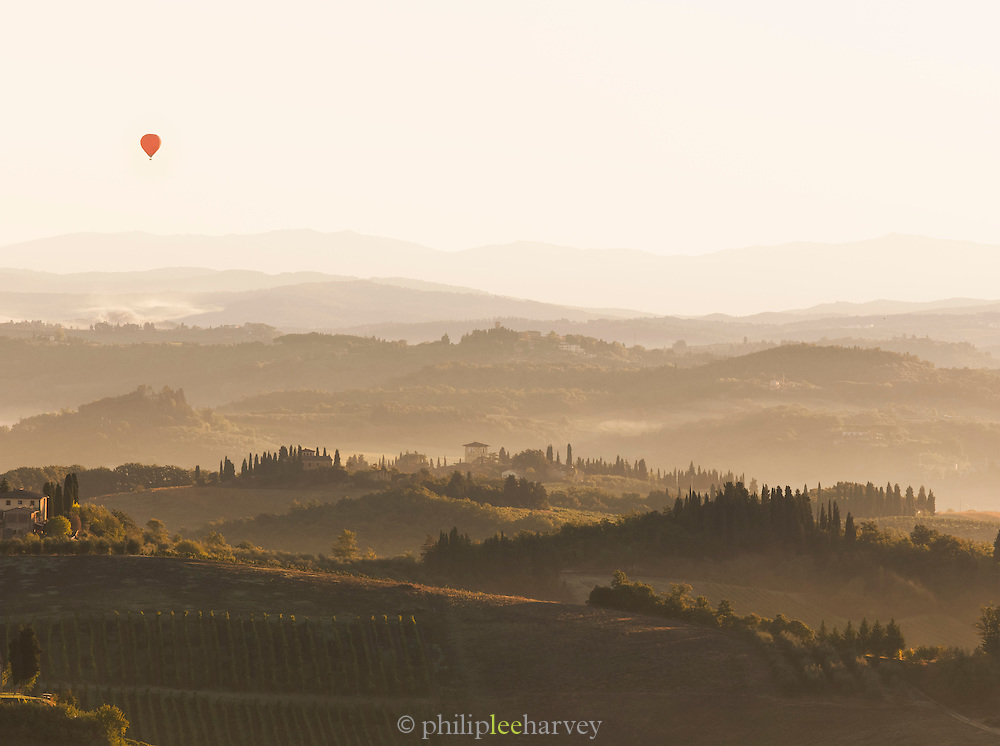 The beautiful rolling hills of Tuscany, with the iconic silhouettes of Cypress trees, in the landscape near San Gimignano, Italy