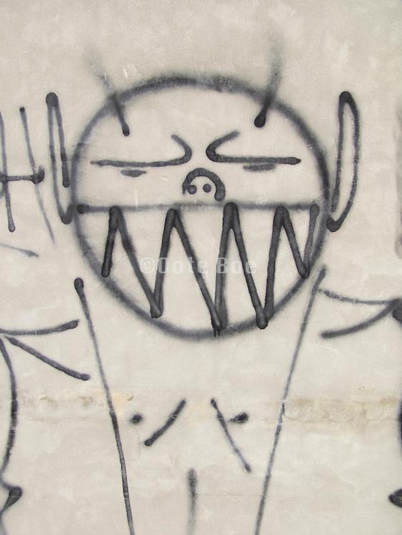 a big smiling graffiti portrait on a gray wall